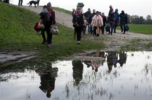 A group of migrants walk past a puddle after crossing from Croatia, in Brezice, Slovenia Monday, Oct. 19, 2015. Croatia's interior minister has rejected Slovenia's accusations that Croatia broke an agreement on limiting the numbers crossing their border t