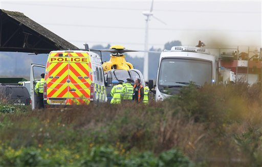 Police seen near the scene of a jet crash, in Redmere, Cambridgeshire, England, Wednesday Oct. 21, 2015.