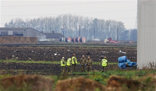 Defence personnel stand in a field, at the scene of a jet crash, in Redmere, Cambridgeshire, England, Wednesday Oct. 21, 2015.