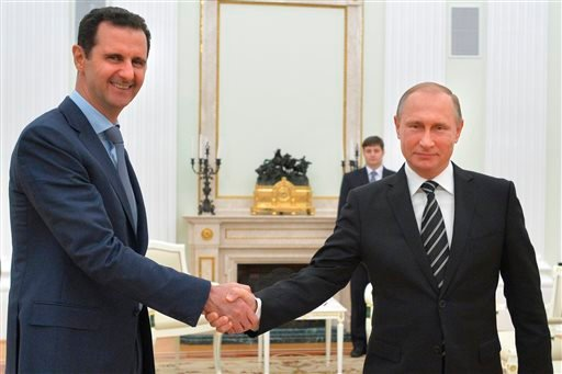 In this photo taken on Tuesday, Oct. 20, 2015, Russian President Vladimir Putin, right, shakes hand with Syria President Bashar Assad in the Kremlin in Moscow, Russia. Assad has traveled to Moscow in his first known trip abroad since the war broke out in