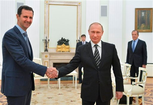 In this photo taken on Tuesday, Oct. 20, 2015, Russian President Vladimir Putin, center, shakes hand with Syrian President Bashar Assad as Russian Foreign Minister Sergey Lavrov, right, looks on in the Kremlin in Moscow, Russia. President Bashar Assad was
