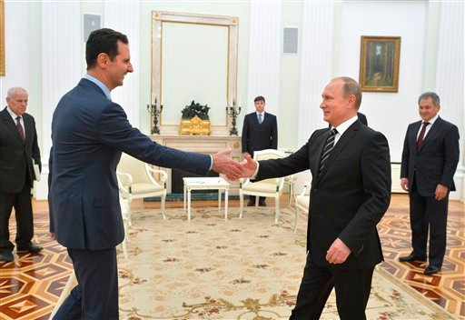 In this photo taken on Tuesday, Oct. 20, 2015, Russian President Vladimir Putin, right, shakes hand with Syrian President Bashar Assad in the Kremlin in Moscow, Russia. Assad was in Moscow, in his first known trip abroad since the war broke out in Syria i