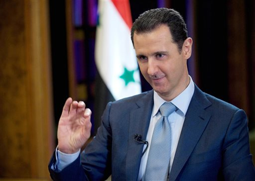 In this Tuesday, Feb. 10, 2015, file photo released by the Syrian official news agency SANA, Syrian President Bashar Assad gestures during an interview with the BBC in Damascus, Syria. Syrian state media says Assad has met his Russian counterpart, Vladimi