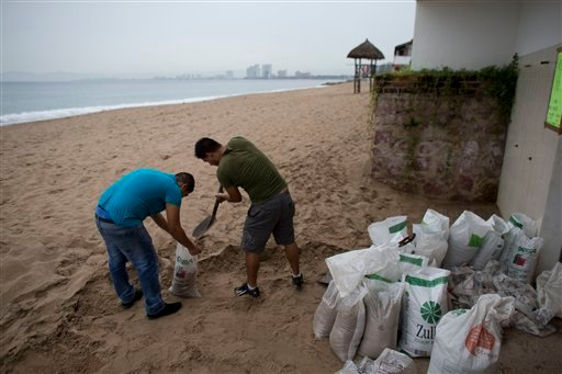 Men fill small bags with sand from the beach as they prepare for the arrival of Hurricane Patricia in Puerto Vallarta, Mexico, Friday, Oct. 23, 2015.