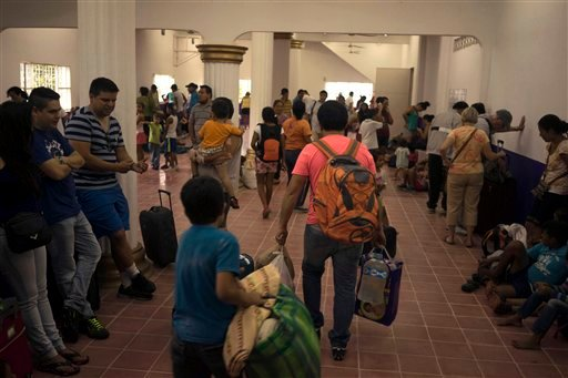 People arrive at a makeshift shelter set up in preparation for the arrival of Hurricane Patricia in the Pacific resort city Puerto Vallarta, Mexico, Friday, Oct. 23, 2015. (AP Photo/Cesar Rodriguez)