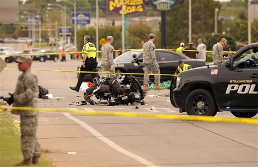 A damaged police motorcycle rests in the intersection after a vehicle crashed into a crowd of spectators during the Oklahoma State University homecoming parade, causing multiple injuries, on Saturday, Oct. 24, 2015 in Stillwater, Oka.(AP Photo/Brody Schmi