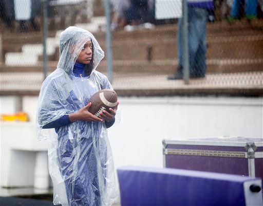 Texas College cheerleader sophomore Shan Moore wears a poncho on the sideline an NCAA college football game between Arizona Christian and Texas College, Saturday Oct. 24, 2015, in Tyler, Texas. Southeast Texas was bracing for heavy rain late Saturday and