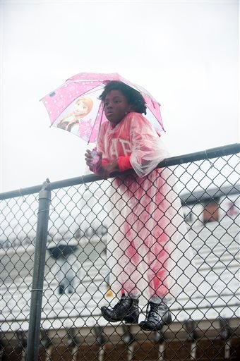 Jordyn Gil holds an umbrella as she watches an NCAA college football game between Arizona Christian and Texas College, Saturday Oct. 24, 2015, in Tyler, Texas. Southeast Texas was bracing for heavy rain late Saturday and into Sunday as the remnants of Hur