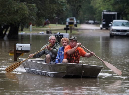 J.B. Neckar, right, and his brother Johnny Neckar, left, paddle their mother Gelene Neckar, center, from her flooded home near Downsville, Texas, Saturday, Oct. 24, 2015. Heavy rains have forced parts of the Brazos River out of its banks and endangering h