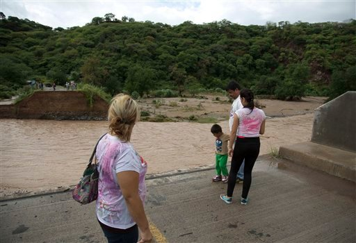 People stand at the edge of a collapsed bridge, overlooking the Ameca River in Cofradia, some 200 km northwest of Guadalajara, Mexico, Saturday, Oct. 24, 2015. Hurricane Patricia made landfall Friday on a sparsely populated stretch of Mexico's Pacific coa