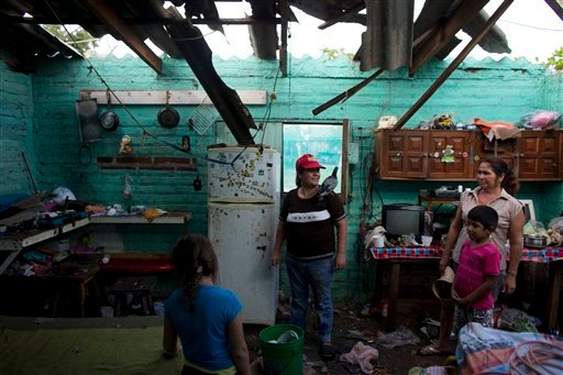Josefina Magana Ruiz, center, surveys her home damaged by Hurricane Patricia, in La Fortuna, Mexico, Saturday, Oct. 24, 2015. Hurricane winds tore off much of the roof of the two-room home where seven people live, soaking mattresses and destroying belongi