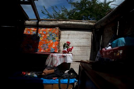 Artificial flowers sit on a makeshift shelf in the home of Sergio Reyna Ruiz, a day after Hurricane Patricia tore off a section of the roof, in La Fortuna, Mexico, Saturday, Oct. 24, 2015. Just next door the home of Reyna's sister, suffered much more dama