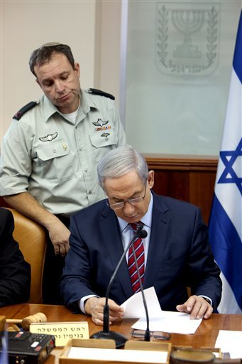 Israel's Prime Minister Benjamin Netanyahu reads notes from his military secretary Brigadier General Eliezer Toledano, left, during the weekly cabinet meeting at his office, in Jerusalem, Sunday, Oct. 25, 2015. (Gali Tibbon/Pool Photo via AP)