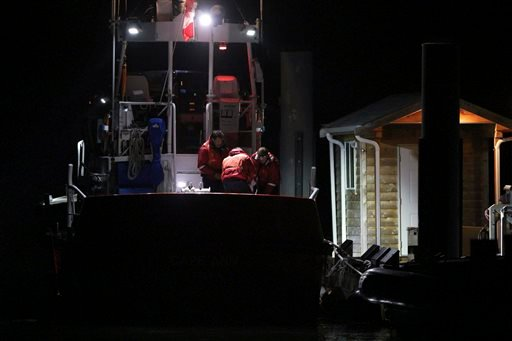 Canadian Coast Guard crew arrive at a dock in Tofino, west coast of Vancouver, Canada, early Monday, Oct. 26, 2015, following a search and rescue operation. (Chad Hipolit/The Canadian Press via AP)