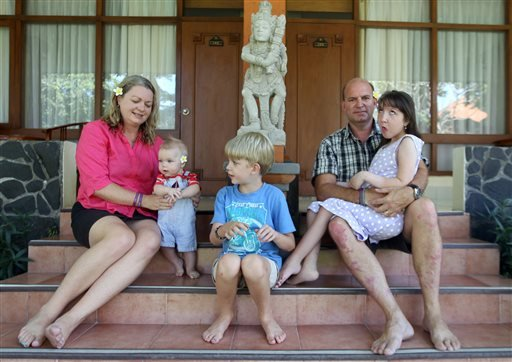 In this Aug. 12, 2015 photo, Jenn, left, and Mark Hooper sit for a photo with their three children, from left, Cody, Zak and Charley in Bali, Indonesia. (AP Photo/Firdia Lisnawati)