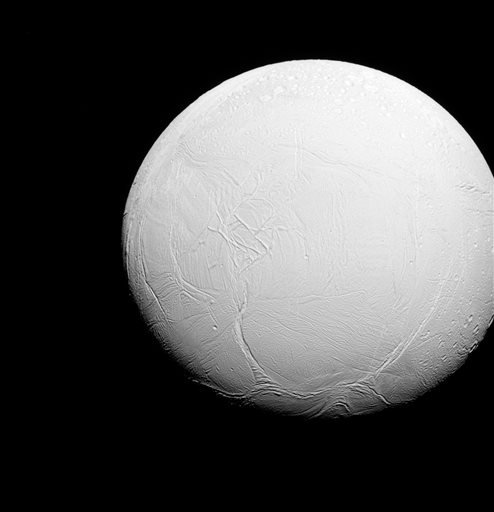 This July 27, 2015 photo made by the Cassini spacecraft shows the moon Enceladus orbiting the planet Saturn. To the north, top, the terrain is covered in impact craters, much like other icy moons, but to the south, the record of impact cratering is much m