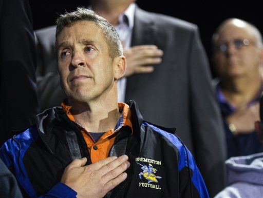 Bremerton assistant football coach Joe Kennedy, recently placed on administrative leave due to his prayers on the football field after games, listens to the national anthem from the stands at Memorial Stadium in Bremerton, Wash.