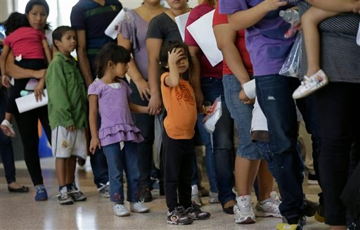 In this June 20, 2014, file photo, immigrants who entered the U.S. illegally stand in line for tickets at the bus station after they were released from a U.S. Customs and Border Protection processing facility in McAllen, Texas.