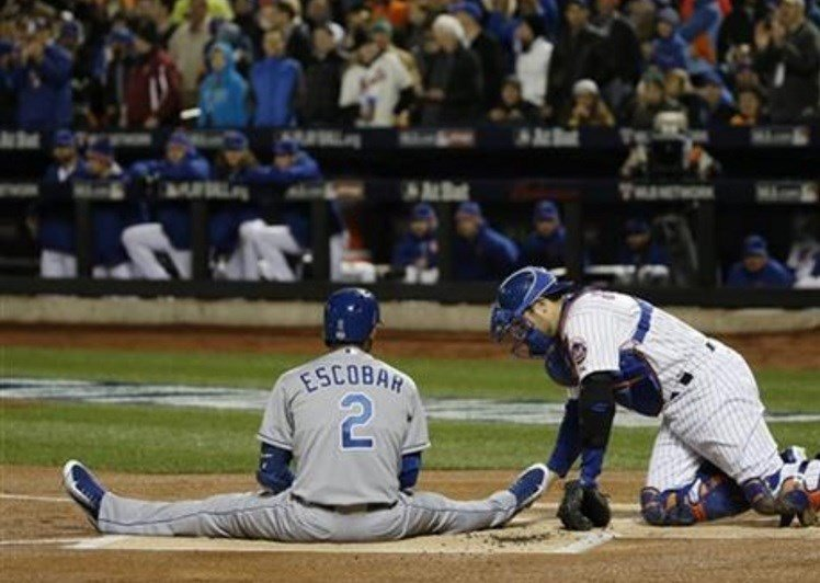 Kansas City Royals' Alcides Escobar (2) sits on the infield after being nearly hit by a pitch from New York Mets pitcher Noah Syndergaard during the first inning of Game 3 of the Major League Baseball World Series Friday, Oct. 30, 2015, in New York.  AP