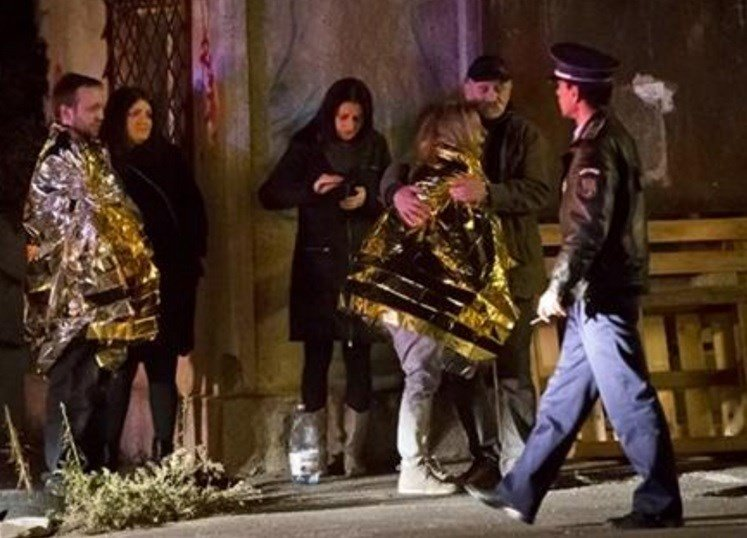 A survivor of an explosion that occurred in a club in Bucharest, Romania, cries, wrapped in a thermal blanket outside the blast scene early Saturday, Oct. 31, 2015.