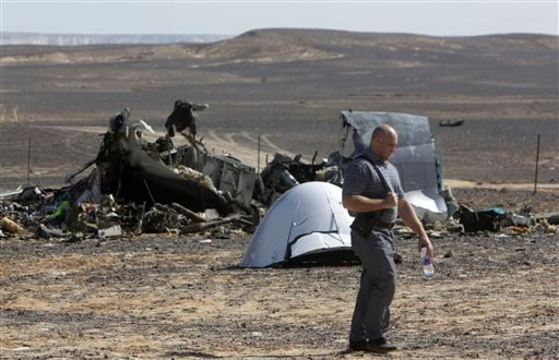 A Russian investigator walks near wreckage a day after a passenger jet bound for St. Petersburg, Russia, crashed in Hassana, Egypt, on Sunday, Nov. 1, 2015. The Metrojet plane, bound for St. Petersburg in Russia, crashed 23 minutes after it took off from