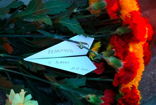 """A white paper plane with the writing reading """"Belarus is with you"""" lays among flowers in front of the Russian Embassy brought by Belarusians to pay tribute to victims of a Russian plane crash in Minsk, Belarus, Sunday, Nov.1, 2015. A Russian passenger pla"""