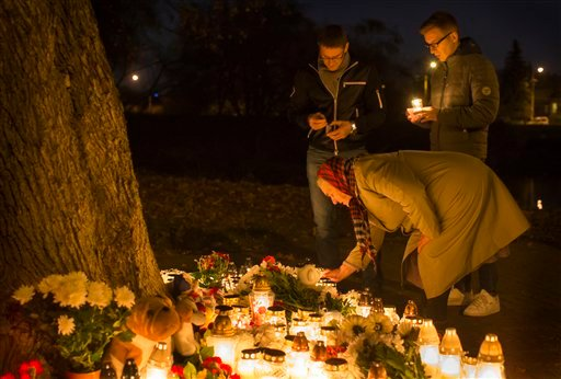 People light candles to pay tribute to victims of a Metrojet plane crashed in Egypt, in front of the Russia's Embassy in Vilnius, Lithunia, Sunday, Nov. 1, 2015. The Metrojet plane, bound for St. Petersburg in Russia, crashed 23 minutes after it took off