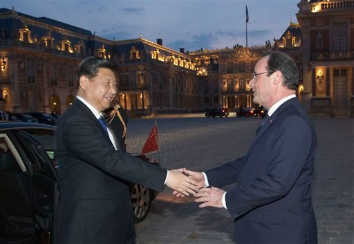 In this March 27, 2014 file photo, Chinese President Xi Jinping, left, is welcomed by French President Francois Hollande, right, at the Chateau de Versailles, in Versailles, west of Paris, for a concert and dinner. The French President Francois Hollande h