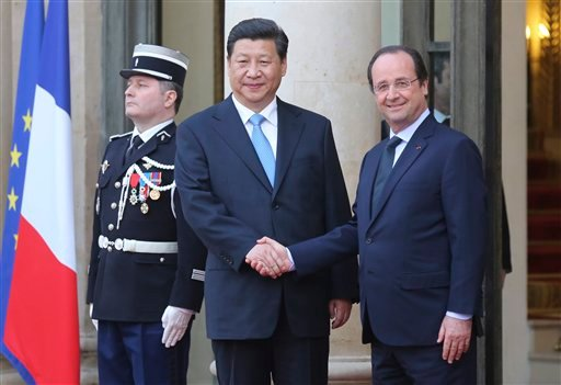 In this March 26, 2014 file photo, French President Francois Hollande, right, takes leave of Chinese President Xi Jinping following their meeting at the Elysee Palace in Paris, France. The French President Francois Hollande hopes to give a push to climate