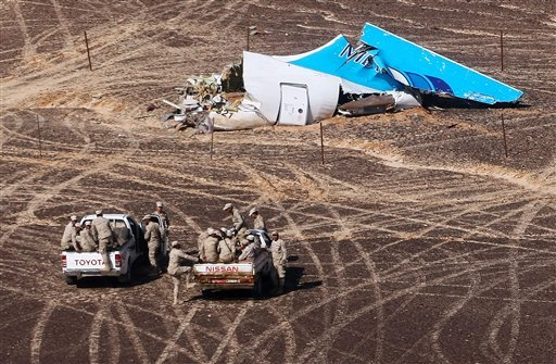 In this photo made available Monday, Nov. 2, 2015, and provided by Russian Emergency Situations Ministry, Egyptian Military on cars approach a plane's tail at the wreckage of a passenger jet bound for St. Petersburg in Russia that crashed in Hassana, Egyp