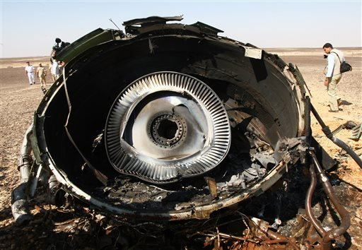 In this photo made available Monday, Nov. 2, 2015, and provided by Russian Emergency Situations Ministry, Egyptian Military experts examine a piece of an engine at the wreckage of a passenger jet bound for St. Petersburg in Russia that crashed in Hassana,