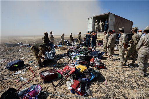 In this Monday, Nov. 2, 2015 file photo provided by the Russian Ministry for Emergency Situations, Egyptian soldiers collect personal belongings of plane crash victims at the crash site of a passenger plane bound for St. Petersburg in Russia that crashed