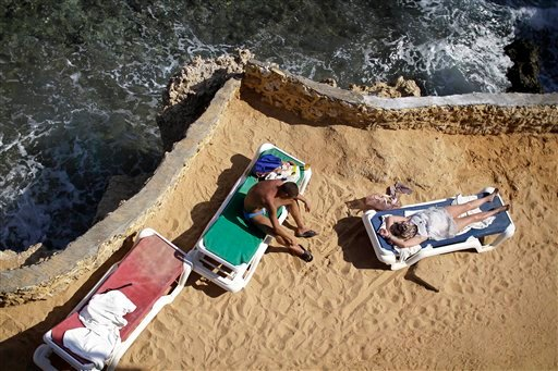 Tourists sunbathe on the shore of the Red Sea at a hotel that is hosting many travelers waiting to be evacuated from the resort city of Sharm el-Sheikh, south Sinai, Egypt, Saturday, Nov. 7, 2015. Russia has suspended all flights to Egypt, joining the U.K
