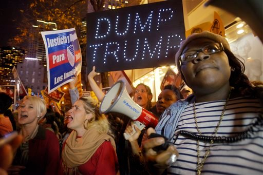 """Sasha Murphy, of the ANSWER Coalition, leads demonstrators in a chant during a protest against Republican presidential candidate Donald Trump's hosting """"Saturday Night Live"""" in New York, Saturday, Nov. 7, 2015. Despite a 40-year history of lampooning poli"""