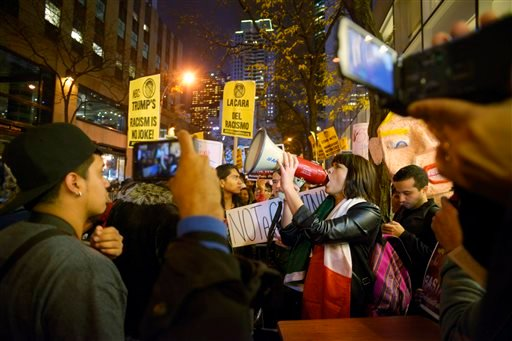 """Karina Garcia, of the ANSWER Coalition, uses a megaphone to lead demonstrators in a chant during a protest against Republican presidential candidate Donald Trump's hosting """"Saturday Night Live"""" in New York, Saturday, Nov. 7, 2015. Despite a 40-year histor"""
