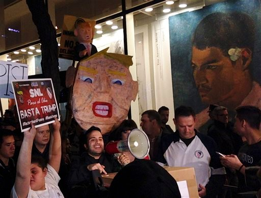 """Demonstrators march to protest Donald Trump's views on immigration hours before he hosts """"Saturday Night Live,"""" Saturday, Nov. 7, 2015, in New York. Dozens of protesters held signs and chanted Saturday evening as they marched from Trump Tower to NBC's stu"""