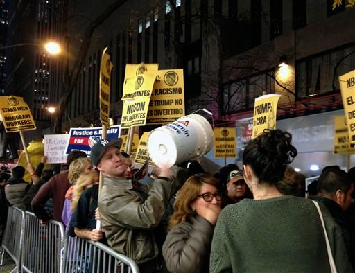 "Demonstrators march to protest Donald Trump's views on immigration hours before he hosts ""Saturday Night Live,"" Saturday, Nov. 7, 2015, in New York. Dozens of protesters held signs and chanted Saturday evening as they marched from Trump Tower to NBC's stu"