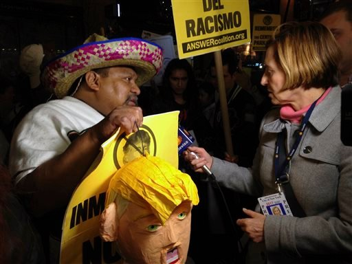 "A member of the media interviews a demonstrators who was participating in a protest over Donald Trump's views before Trump hosts ""Saturday Night Live,"" Saturday, Nov. 7, 2015, in New York. Dozens of protesters held signs and chanted Saturday evening as th"