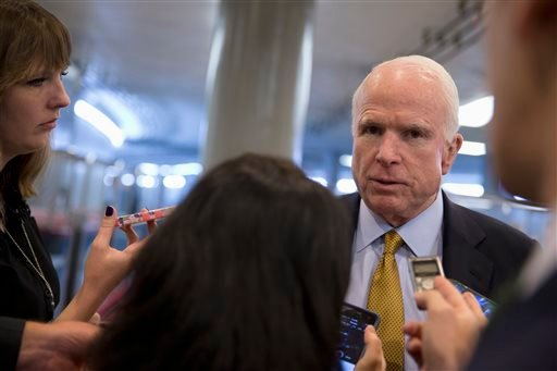In this Oct. 20, 2015, photo, Senate Armed Service Committee Chairman Sen. John McCain, R-Ariz., talks to reporters near the subway on Capitol Hill in Washington. In the fight against the Islamic State group, members of Congress talk tough on extremism, b