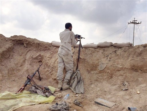 A fighter with Peace Brigades, a Shiite militia group loyal to Shiite cleric Muqtada al-Sadr, takes his combat position outside Samarra, a town north of Baghdad that is home to a major Shiite shrine, 60 miles (95 kilometers) north of Baghdad, Iraq, Sunday