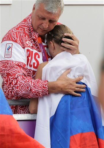 In this Aug. 11, 2012 file photo Russia coach Alexey Melnikov embraces silver-medalist Olga Kaniskina after the 20-kilometers women's race walk at the 2012 Summer Olympics in London. WADA's independent commission said Monday, Nov. 9, 2015 Russia's athleti