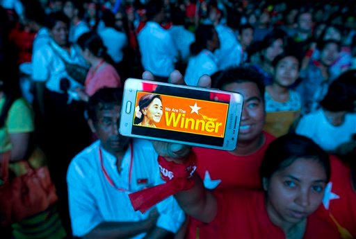 A supporter of Myanmar's National League for Democracy party displays her mobile phone with a picture of Suu Kyi as they gather to celebrate unofficial election results outside the NLD headquarters in Yangon, Myanmar, Monday, Nov. 9, 2015. Opposition lead