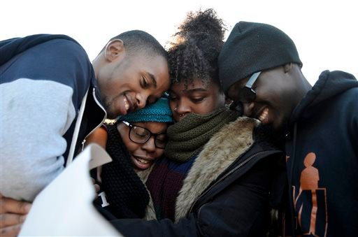 Members of Concerned Student 1950 embrace after the announcement that University of Missouri System President Tim Wolfe would resign Monday, Nov. 9, 2015, in Columbia, Mo. Wolfe resigned Monday with the football team and others on campus in open revolt ov