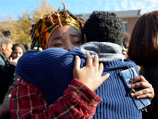 Supporters embrace each other following the announcement that University of Missouri System President Tim Wolfe would resign Monday, Nov. 9, 2015, in Columbia, Mo. Wolfe resigned Monday with the football team and others on campus in open revolt over his h