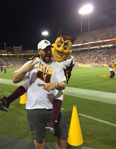 This photo courtesy of David Schapira shows ASU's mascot Sparky jumping on David Schapira at a Arizona State University football game on Sept. 18, 2015 in Tempe, Ariz.