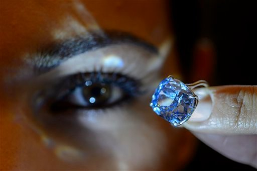 In this Nov. 4, 2015 file photo a Sotheby's employee displays the rare Blue Moon Diamond during a preview at Sotheby's, in Geneva, Switzerland.