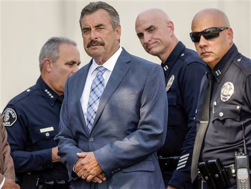 In this Sept. 9, 2015, file photo, Los Angeles Police Chief Charlie Beck, second form left, and unidentified police officers hold a news conference near the site of a covered crime scene.