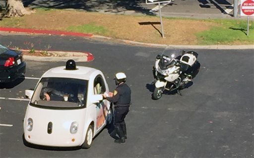 In this Thursday, Nov. 12, 2015 photo provided by Zandr Milewski, a California police officer pulls over a self-driving car specially designed by Google that was being tested on a local road in Mountain View, Calif.