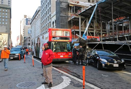 Bystanders look on next to an open-air tour bus, at right under scaffolding, that crashed into a construction site near Union Square Friday, Nov. 13, 2015, in San Francisco.