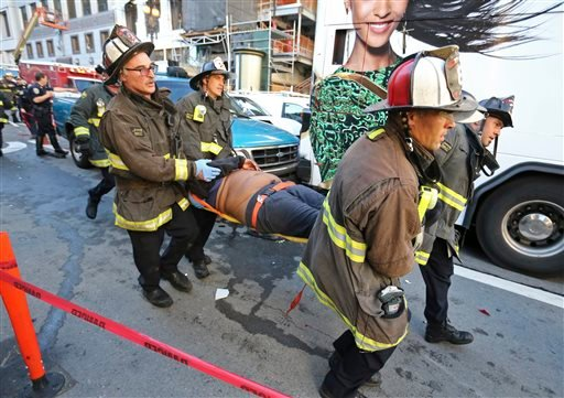 Firemen carry away a passenger injured on an open-air tour bus after it crashed into a construction site near Union Square Friday, Nov. 13, 2015, in San Francisco.